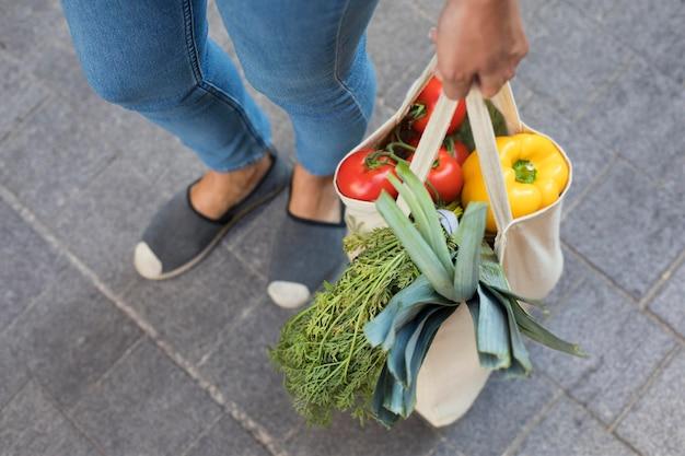 야채와 함께 손을 잡고 가방을 닫습니다