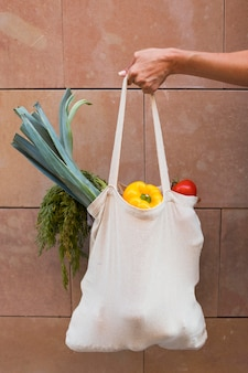 Close up hand holding bag with vegetables