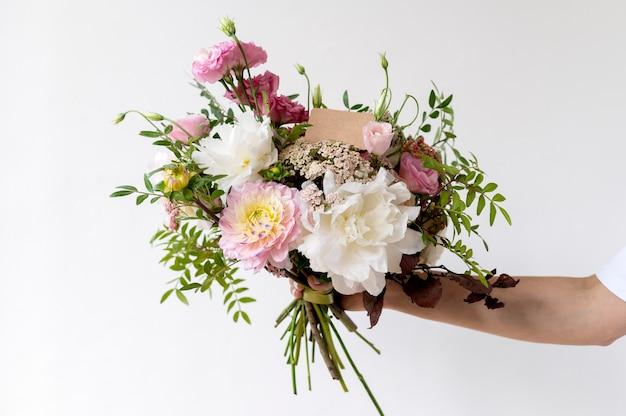 Крупным планом рука держит красивые цветы