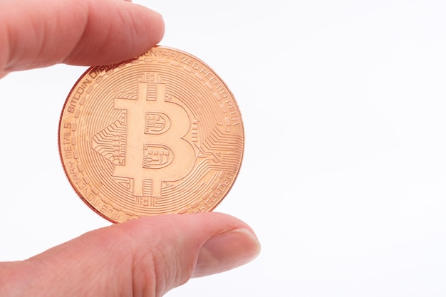 Close-up of a hand holding a bitcoin dcoin on a white background.