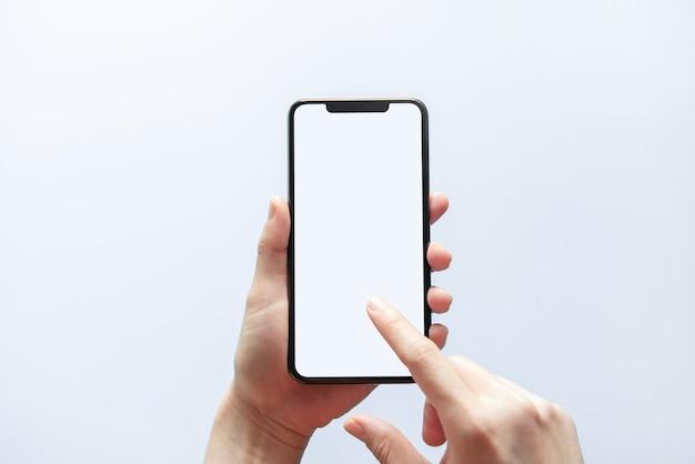 黒い電話の白い画面を持っている手を閉じます。白い壁に分離されました。携帯電話フレームレスデザインコンセプト。