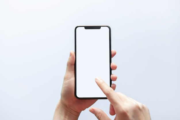 Close up hand holding black phone white screen. isolated on white wall. mobile phone frameless design concept.