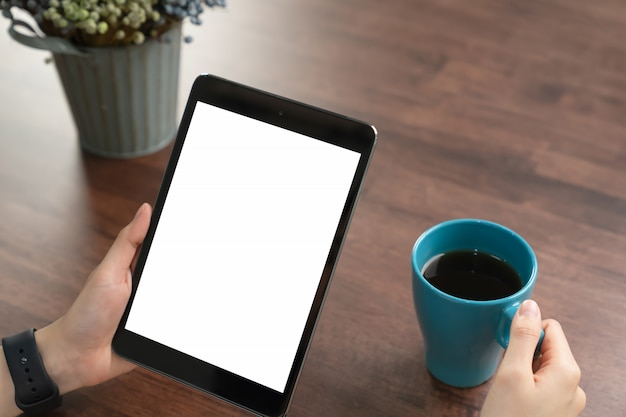 Close-up of hand holding black tablet and coffee on table office.
