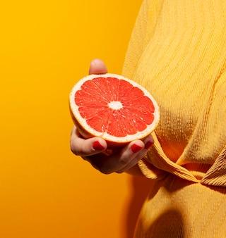 Крупным планом рука держит красный апельсин