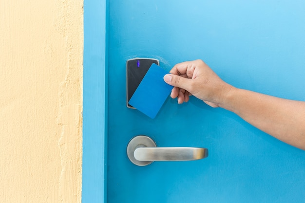 Close up hand holding blue hotel keycard in front of electric door