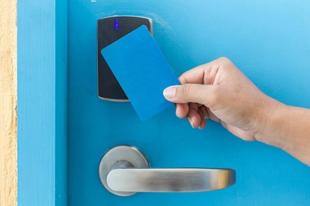 電気ドアの前に青いホテルのキーカードを持って手を閉じます