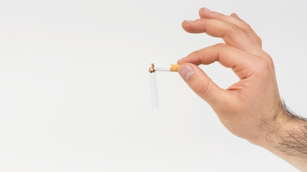 Close-up of hand holding broken cigarette against white backdrop