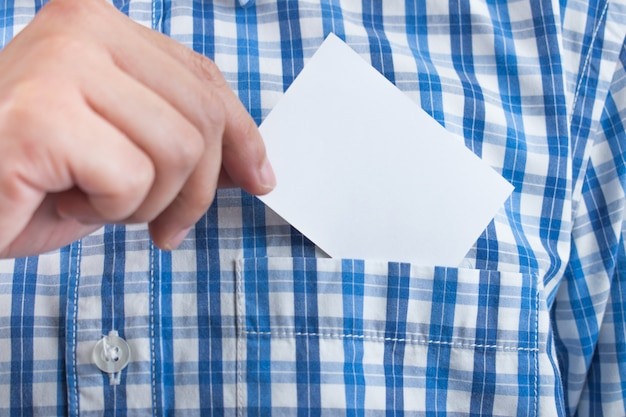 A close up of a hand holding a business card on a shirt