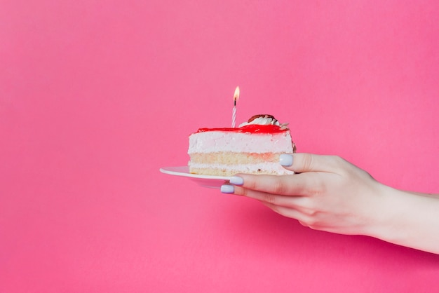 Close-up of hand holding cake slice with lighted candle on plate over the pink background