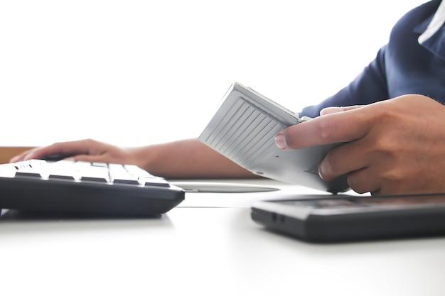 オフィスで電卓を持っている手を閉じます。ワーキングオフィスのコンセプト。仕事のコンセプト。サラリーマン。アカウントまたは財務概念。