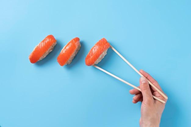 Крупным планом рука, держащая палочки для еды