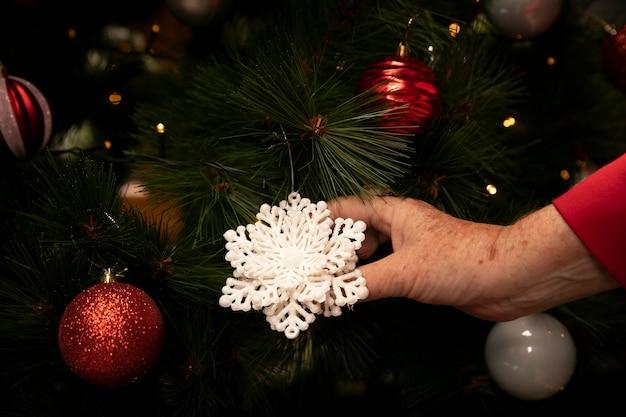 クリスマスの飾りを持っているクローズアップ手