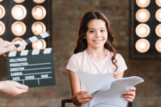 Close-up of hand holding clapper board in front of girl holding scripts