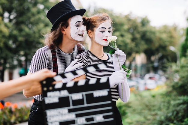 Close-up of a hand holding clapperboard in front of mime couple