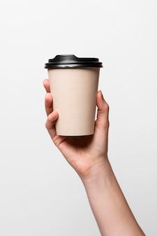 Крупным планом рука держит чашку кофе