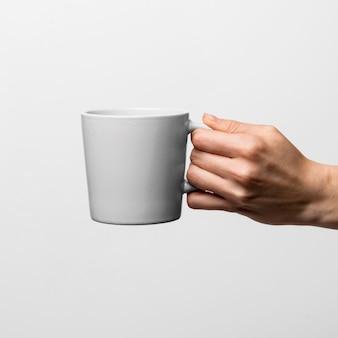 コーヒーマグを持っているクローズアップの手