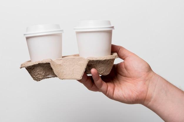 コーヒーを持っているクローズアップの手
