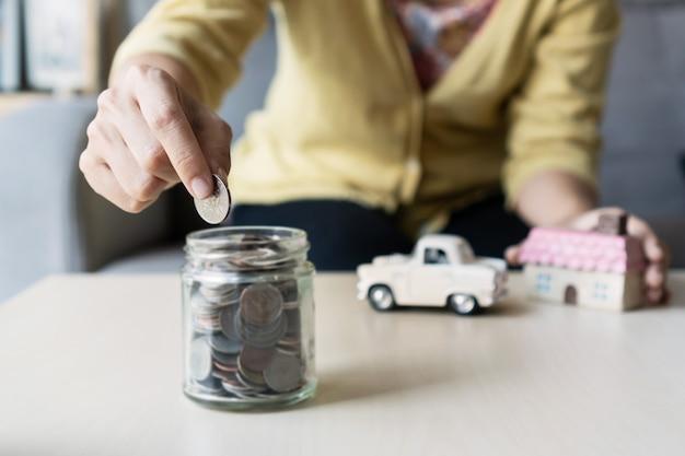 Закройте вверх по руке держа монетку, стог денег, дом игрушки и автомобиль на таблице, сохраняя для будущего, управляйте к успеху, концепция финансов.