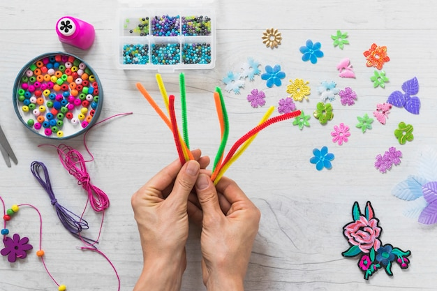 Close-up of hand holding colorful chenille stems with decorative elements