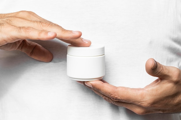 Close-up hand holding cream container