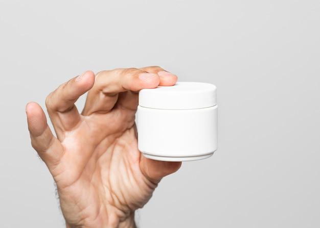 Crema della holding della mano del primo piano