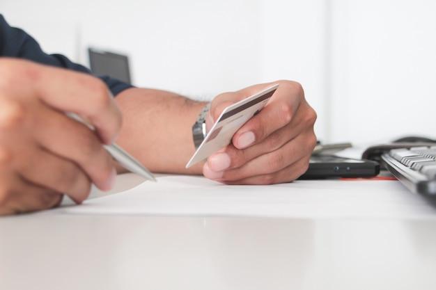 オフィスでクレジットカードまたはatmを持っている手を閉じます。ワーキングオフィスのコンセプト。デジタル決済の概念。サラリーマン。アカウントまたは財務。購入または購入者の概念。