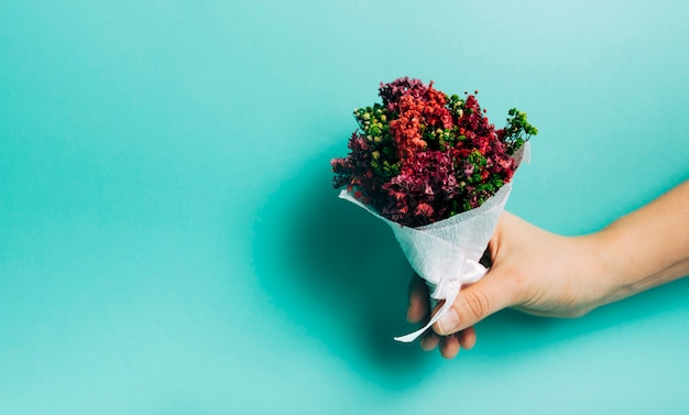 Close-up of hand holding decorative flower bouquet against turquoise background