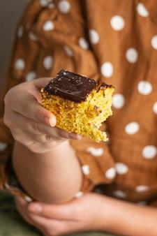 Primo piano mano che tiene una deliziosa torta