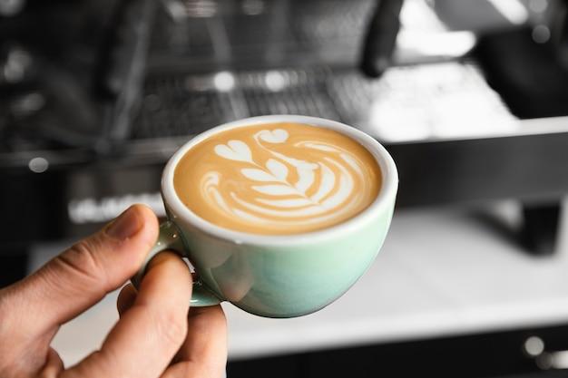 Крупным планом рука держит чашку вкусного кофе