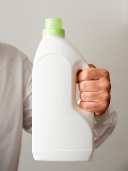 Close-up hand holding detergent bottle mock-up