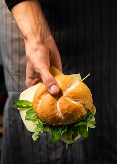 Close-up hand holding fresh bagel