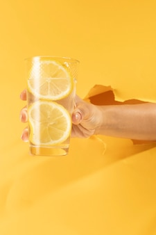 Close-up hand holding glass of lemonade
