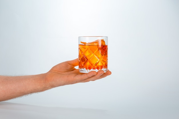 Close up of a hand holding a glass of negroni cocktail on white  with copy space.