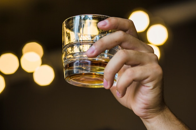 Close-up of hand holding glass of whiskey