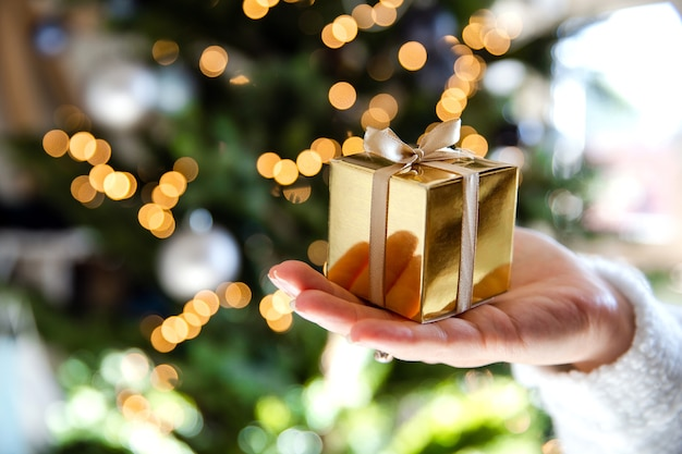 Close up of hand holding a golden gift box with christmas tree and lights