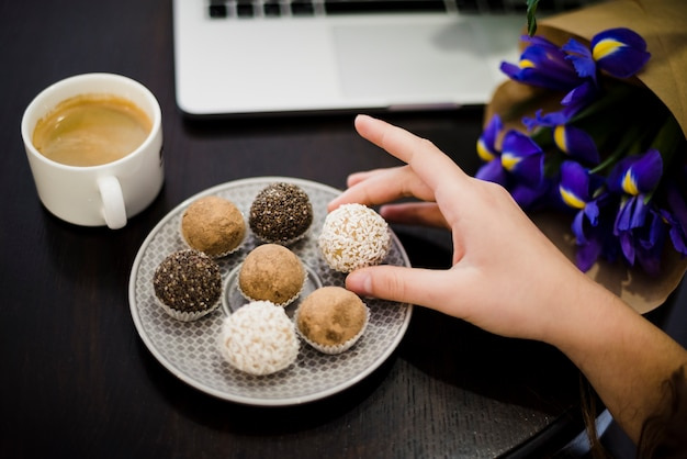 Close-up of hand holding gourmet assorted truffles from plate in black desk