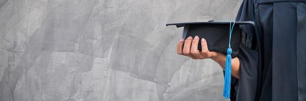 Close up of hand holding graduation hat
