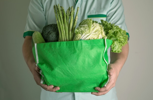 Close up hand holding green grocery bag of mixed the organic green vegetables