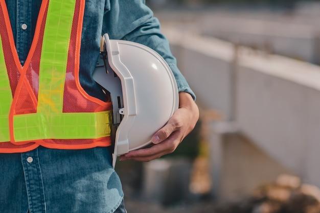 Close up hand holding hard hat helmet building construction engineer, foreman work professional