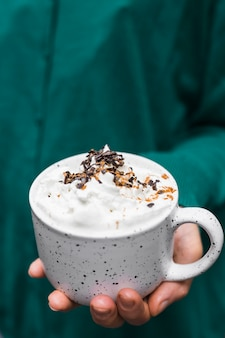 Close-up of hand holding hot chocolate cup with whipping cream and chocolate chips