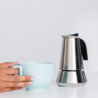 Close-up hand holding kettle and mug