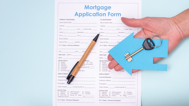 Close-up of a hand holding a key in a blue paper house over a home mortgage application and a pen, top view