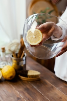 Закройте руку, держащую ломтик лимона