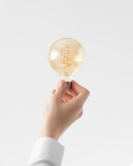 Close up hand holding light bulb