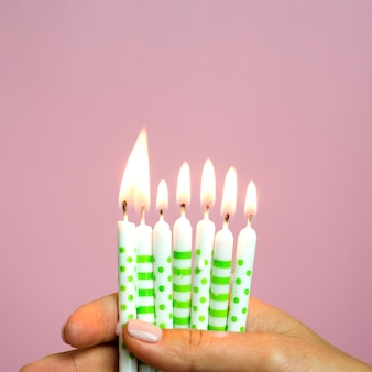 Close-up hand holding little birthday candles