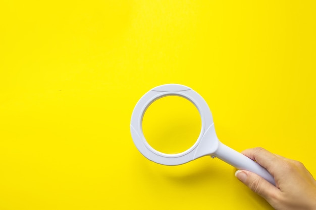 Close up hand holding magnifying glass on yellow background. seo managment.
