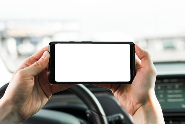 Close-up of hand holding mobile phone with blank white screen in the car