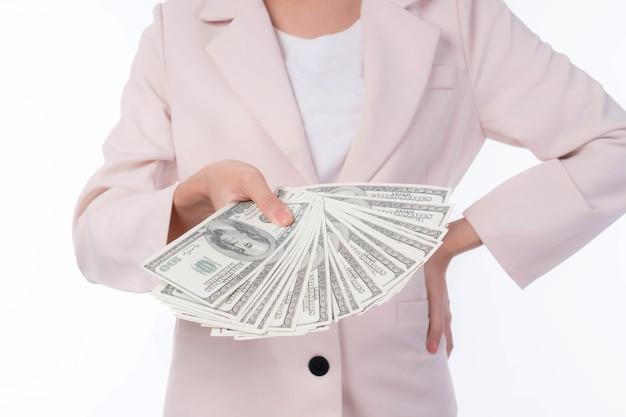 白い背景、ビジネスコンセプトでお金の米ドルの請求書を持っている手をクローズアップ