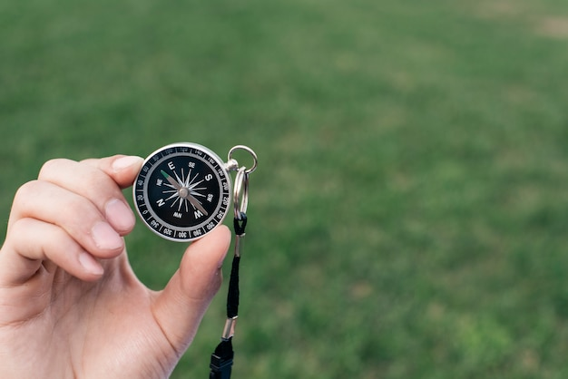 Close-up of hand holding navigational compass against green blurred background