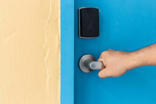 ホテルでステンレス製のドアハンドルを手に持って閉じる